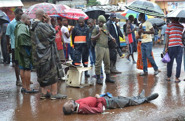 A man suspected of being infected with Ebola lies dead in the street in Conakry, Guinea, on Aug. 21, 2015.