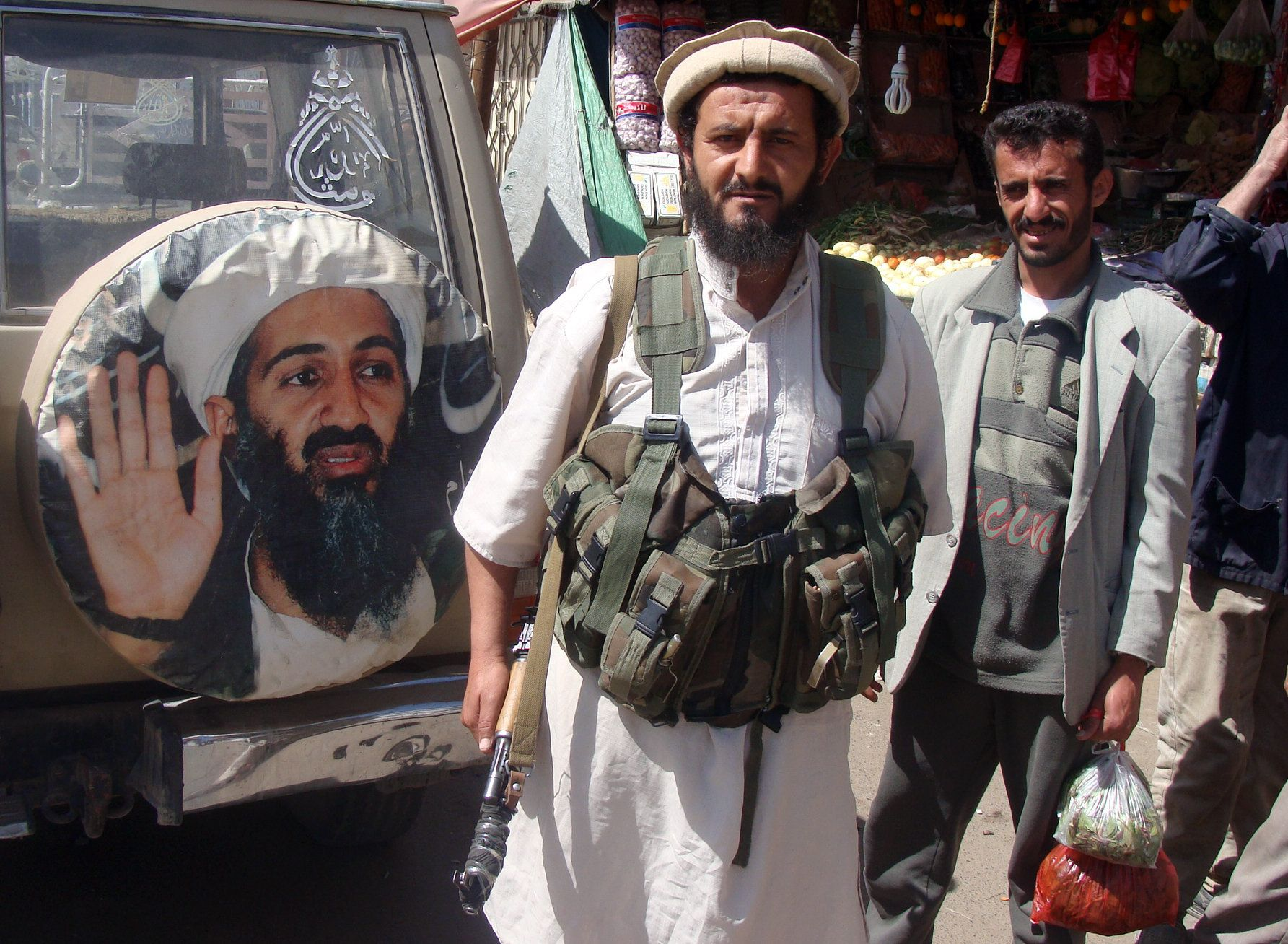 A fighter is seen standing in front of an image of Osama bin Laden, the late head of al-Qaeda, in the town of Rada, 130 kilometres (85 miles) southeast of the capital Sanaa, on January 21, 2012.  Al-Qaeda militants who seized Rada last week are making 'prohibitive' demands for pulling out, a tribal leader said, including applying sharia (Islamic law) and releasing 10 detainees held in the US run held at Guantanamo prison on the island of Cuba. Al-Qaeda-linked militants control a string of towns in Abyan, Shabwa and Marib provinces, but Rada, in al-Bayda province, is the closest they have reached to the capital.    AFP PHOTO/STR (Photo credit should read -/AFP/Getty Images)