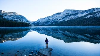 A woman standing on a rock looking out across a perfectly calm lake early in the morning.
