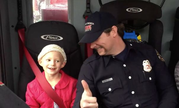 Finley Brown, 6, sits with firefighter Lucas Lambert in a fire truck as they head over to her last round of chemotherapy trea