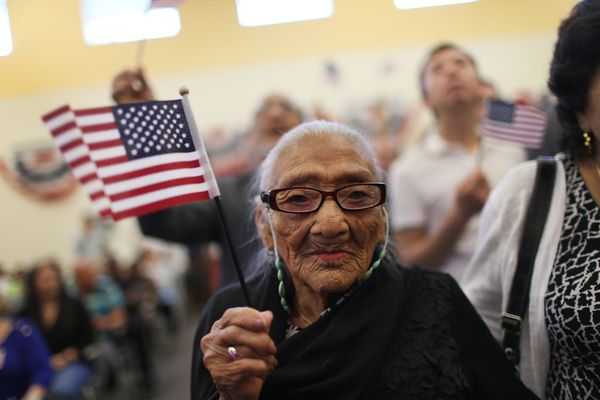 Juana Hernandez holds an American flag as she is sworn in as a naturalized U.S. citizen