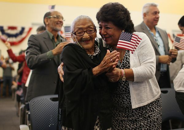 Maria Rosario Corrales (R) hugs her mother, Juana Hernandez, after she had been sworn in as a naturalized U.S. citizen.