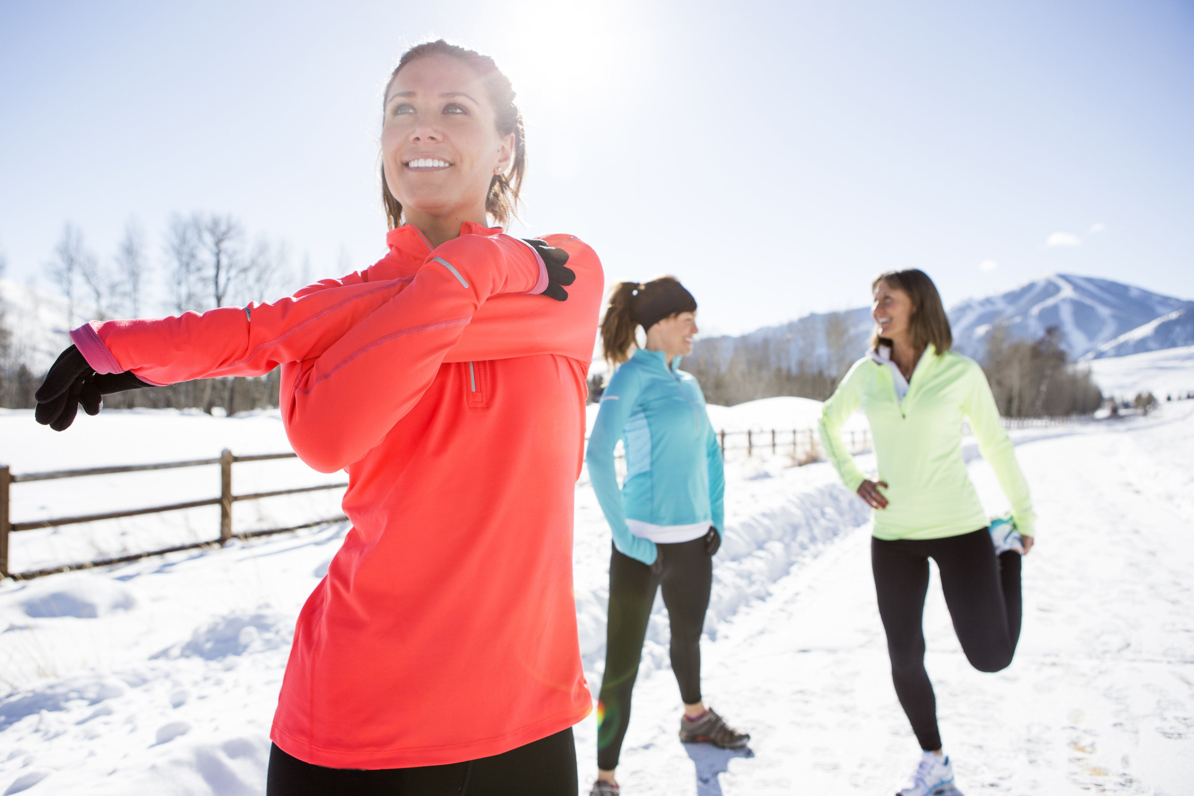 Three women jogging a snowy path in Sun Valley on a beautiful winter day.