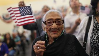 MIAMI, FL - DECEMBER 29:  Juana Hernandez, who is 101 years old and originally from Honduras, holds an American flag as she is sworn in as a naturalized U.S. citizen, at the U.S Citizenship and Immigration Services office on December 29, 2015 in Miami, Florida.  Juana Hernandez was part of the citizenship ceremony that included 140 others and is the last swearing in service of the year for the Miami office.  (Photo by Joe Raedle/Getty Images)