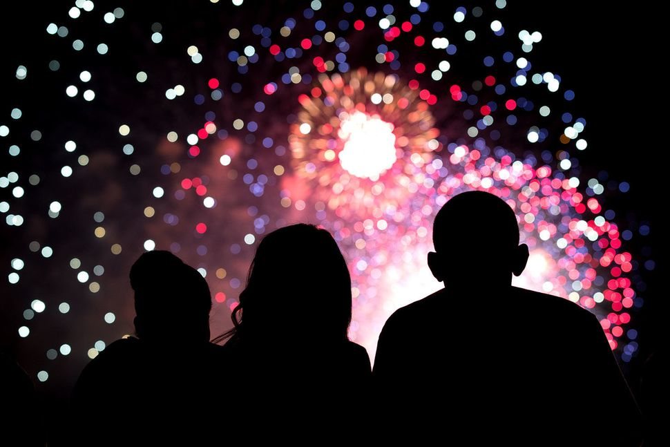 President Barack Obama, First Lady Michelle Obama, and Malia Obama, center, watch the Fourth of July fireworks from the roof