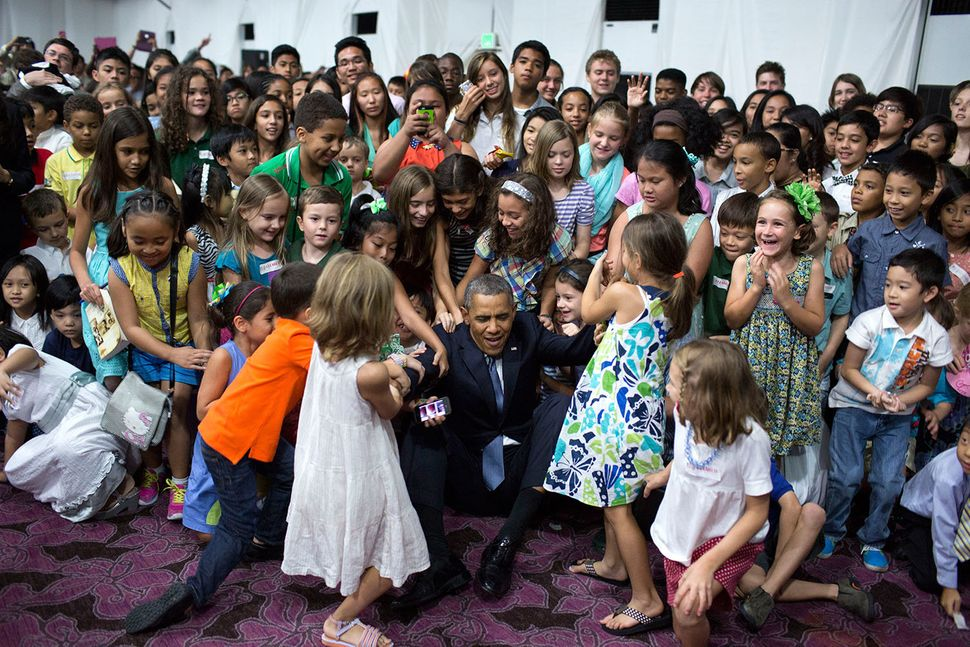 Children help President Barack Obama to his feet after he sat on the floor to have a group photo with them during a U.S. Emba