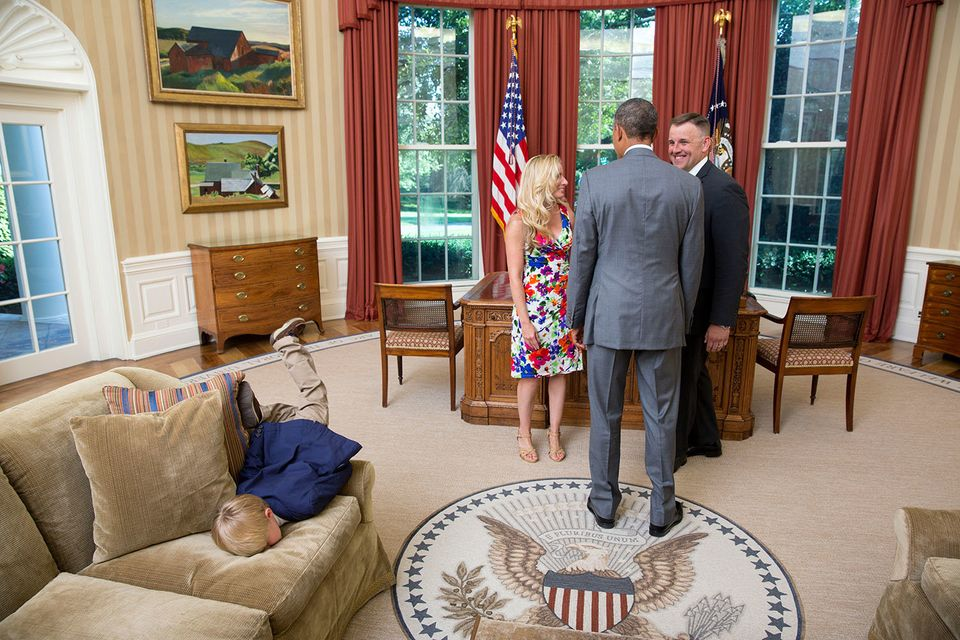 President Barack Obama visits with a departing United States Secret Service agent and his wife as their son dives into a couc