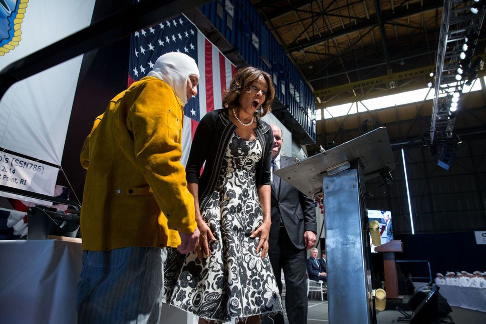 First Lady Michelle Obama reacts to seeing her initials welded onto a steel plate by welder Michael Macomber during a keel-la