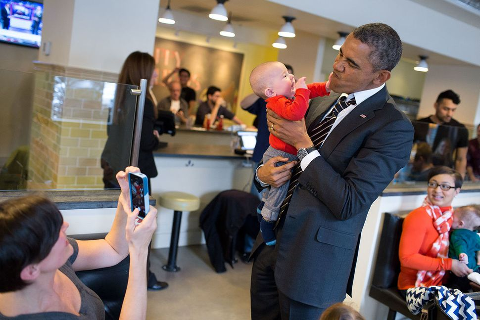 President Barack Obama holds a baby while greeting patrons at The Coupe restaurant in Washington, D.C., Jan. 10, 2014.