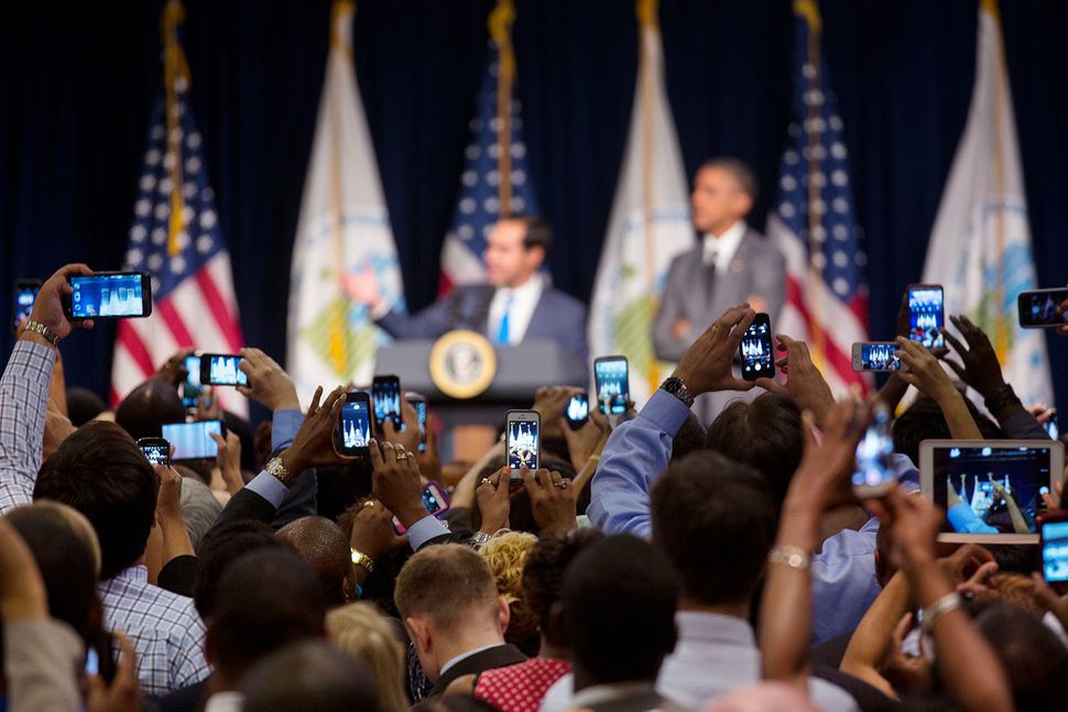 Audience members photograph HUD Secretary Julián Castro introducing President Barack Obama at the Department of Housing and U