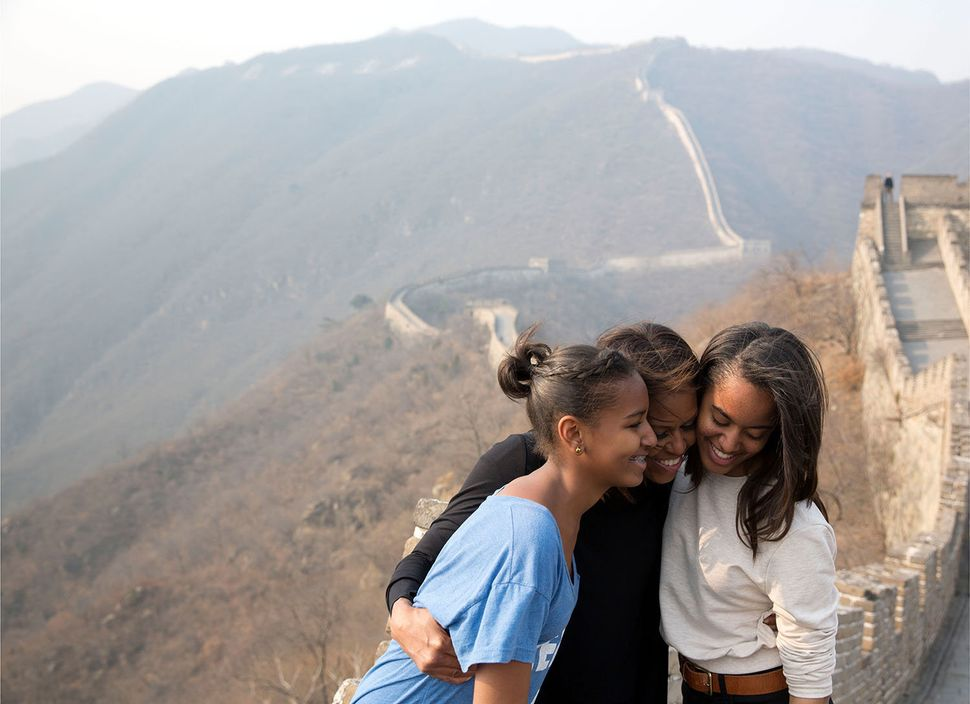 First Lady Michelle Obama hugs daughters Sasha, left, and Malia as they visit the Great Wall of China in Mutianyu, China, Mar