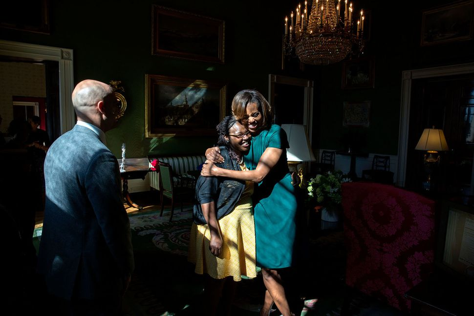 First Lady Michelle Obama hugs introducer Shanese Bryant in the Green Room as they wait with Sam Kass, Executive Director of