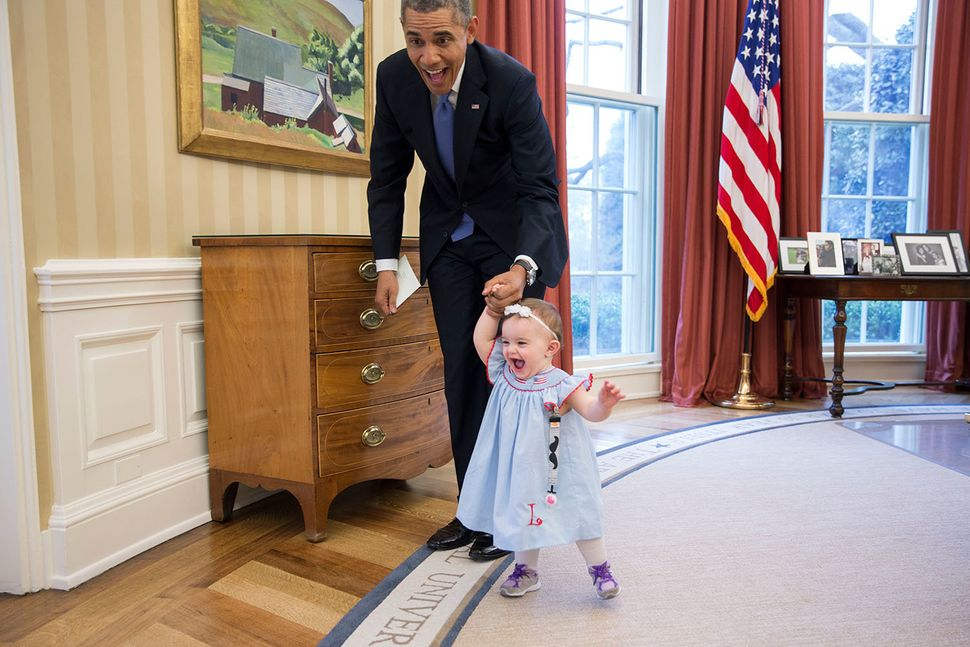 President Barack Obama walks with Lincoln Rose Pierce Smith, the daughter of former Deputy Press Secretary Jamie Smith, in th