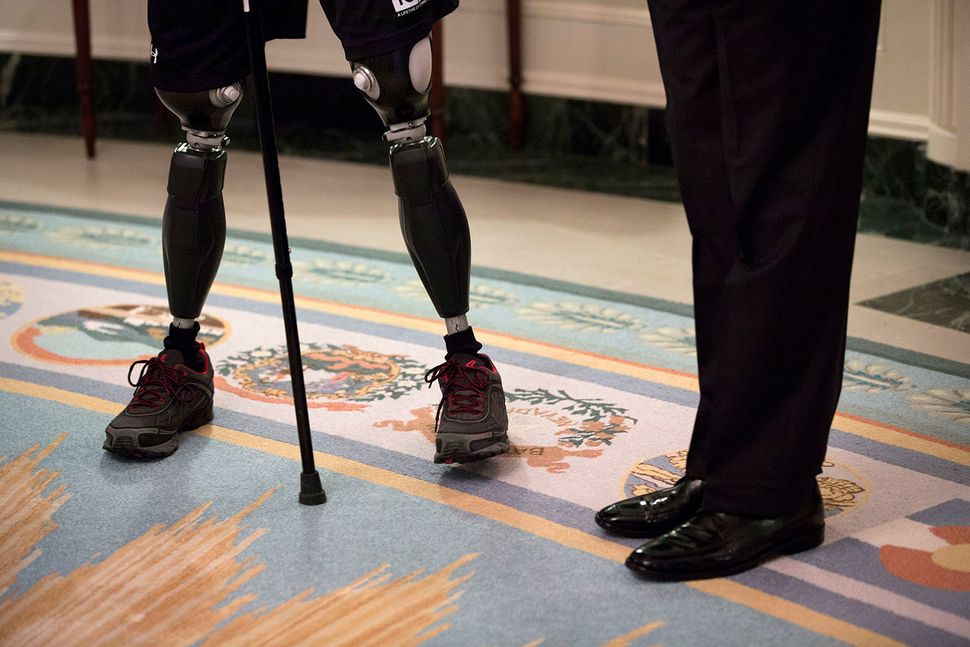 President Barack Obama stands with a rider from the Wounded Warrior Project's Soldier Ride, in the Diplomatic Reception Room