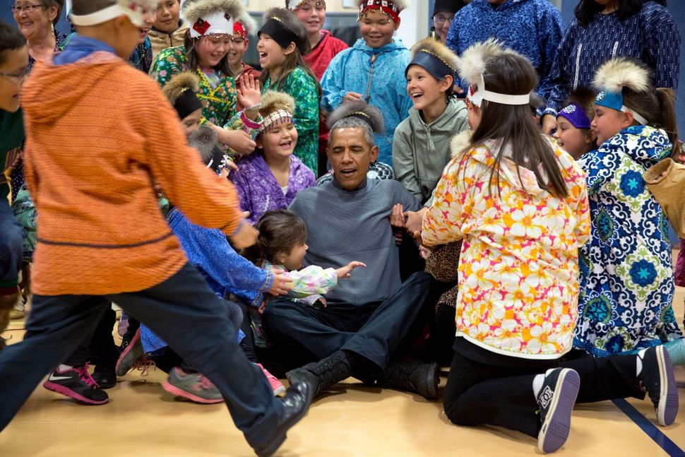 President Obama gets help from students after posing for a photo at Dillingham Middle School in Dillingham, Alaska, on Sept.