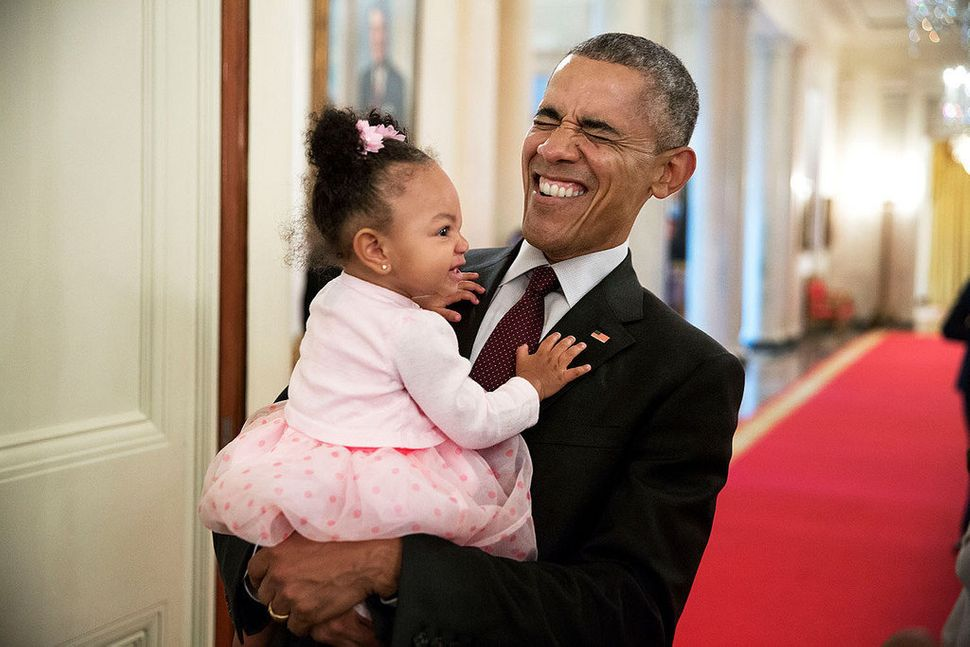 President Barack Obama holds the daughter of former staff member Darienne Page Rakestraw in the Cross Hall of the White House