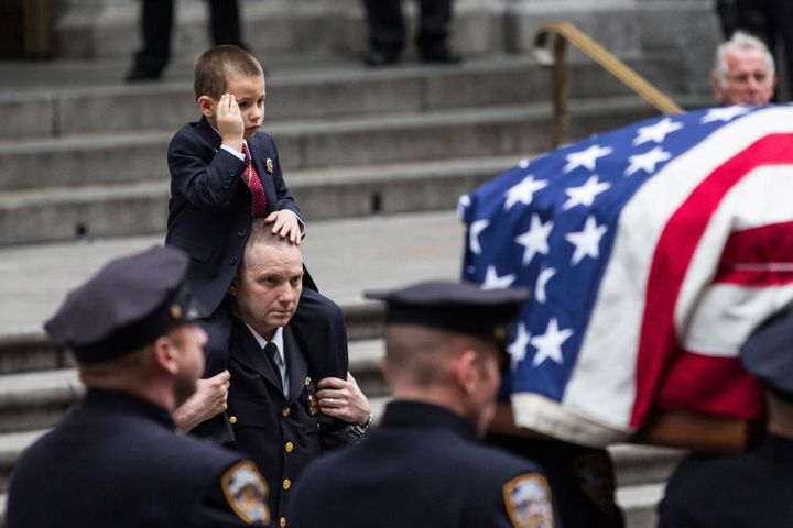 Ryan Lemm, 4, salutes as his father's casket is brought out of St. Patrick's Cathedral in New York City after the officer's f