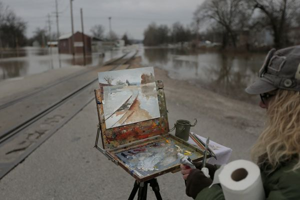 Plein air artist Jan Trager paints a flooded portion of a street on Dec. 30, 2015 in Pacific, Missouri.