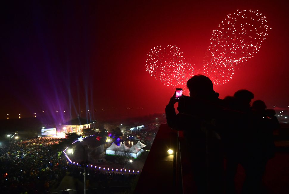 South Koreans take pictures of fireworks during a countdown event to celebrate the new year at Imjingak peace park in the bor