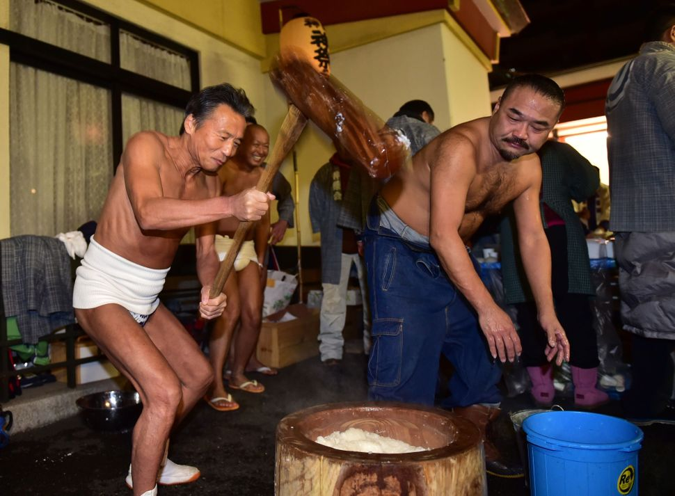 Japanese men pound steamed rice into a mochi rice cake to celebrate the new year at the Kanda shrine in Tokyo on Jan. 1, 2016