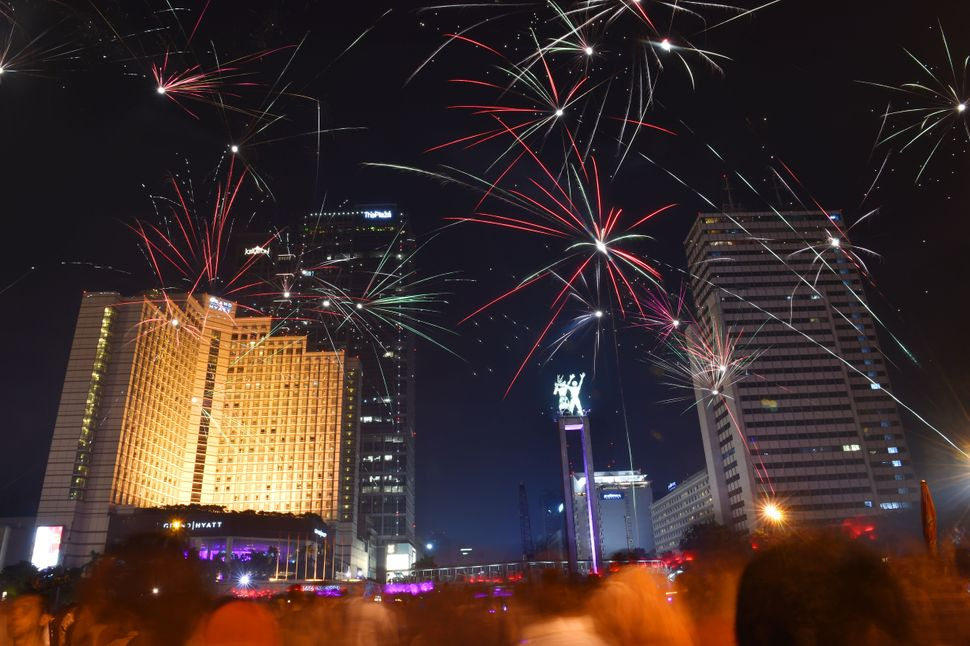 Indonesians gather and take a look at fireworks during a countdown event to celebrate the new year in Jakarta on Dec. 31, 201