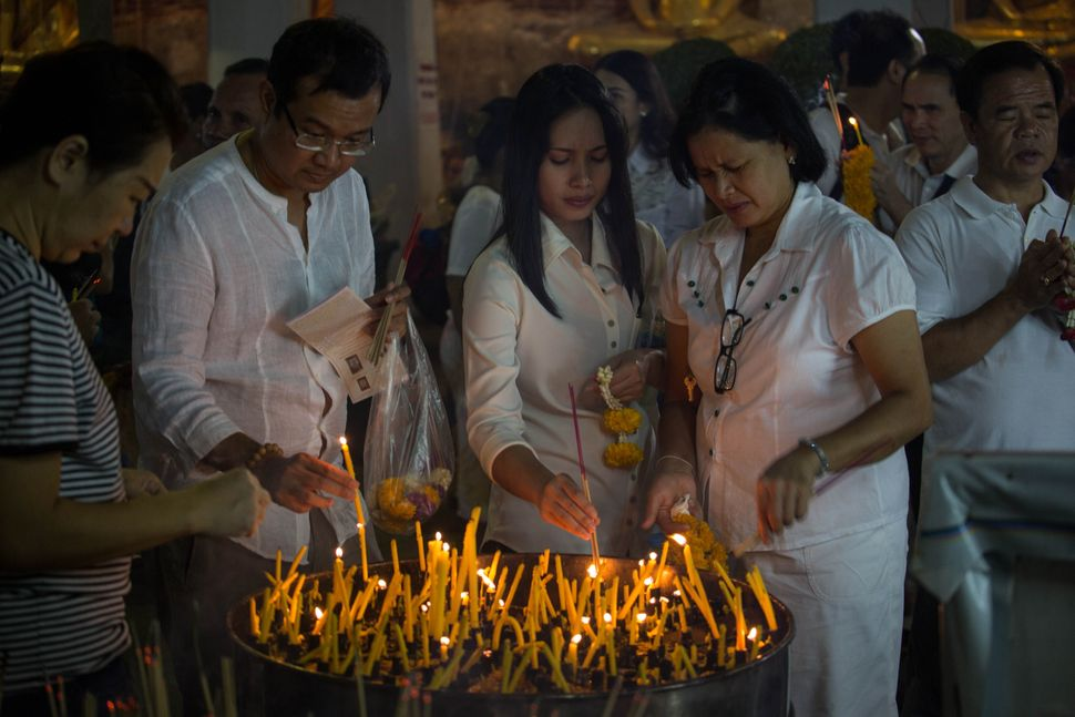 Devotees light up candles as they pray with buddhist monks to celebrate the new year 2016 at Wat Su Thatsana Temple in Bangko