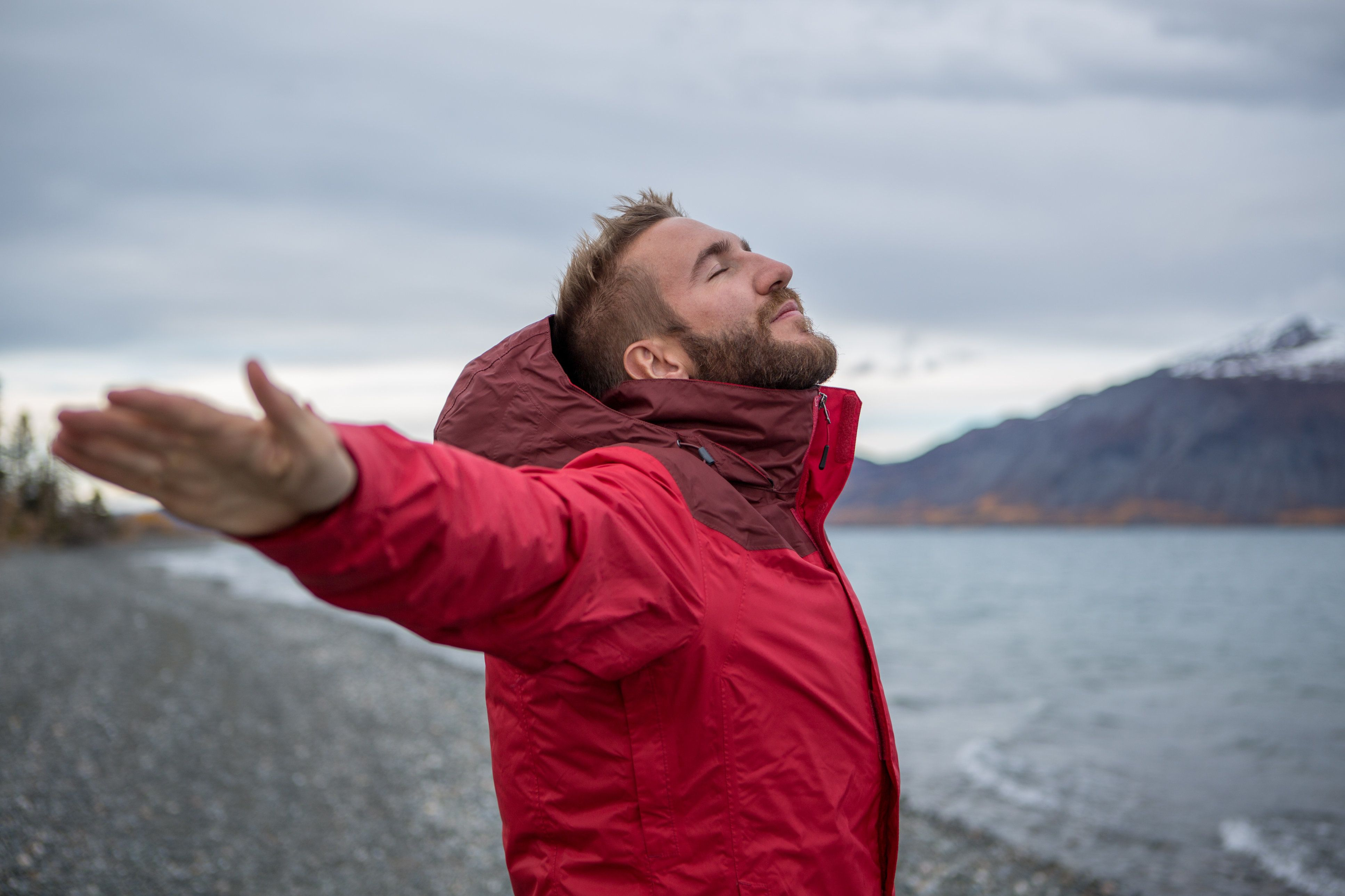 Young cheerful man by the lake enjoying nature. Arms outstretched for positive emotion.