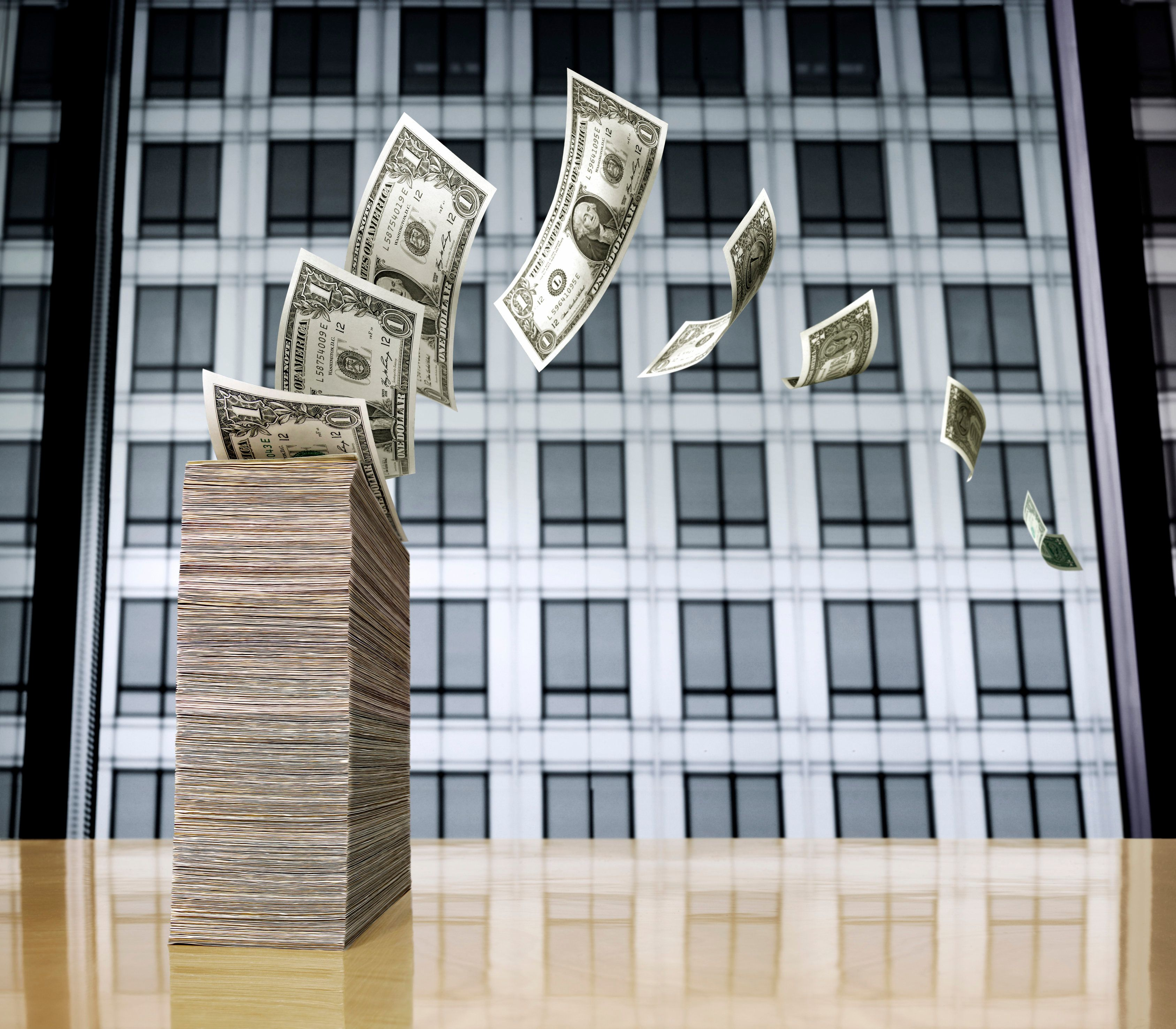 A stack of one dollar bills on a highly polished table in a high rise building with an adjacent building as a background.  The bills are blowing away from camera.