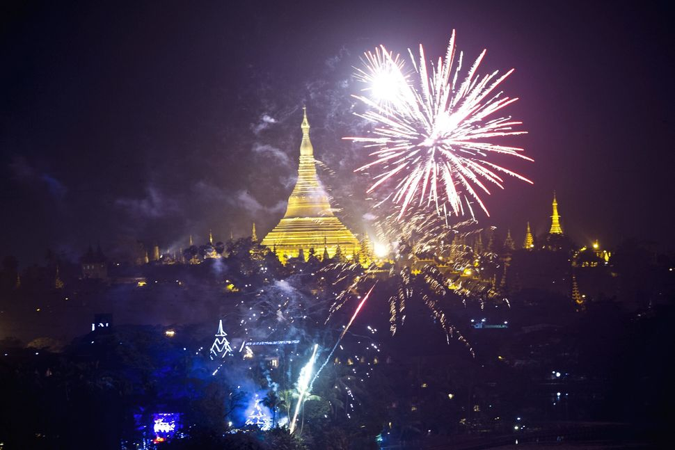 Fireworks are seen near the Myanmar landmark Shwedagon pagoda during the new year countdown at the Kandawgyi Park in Yangon o