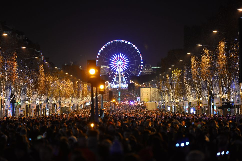 PARIS, FRANCE - JANUARY 01 : People attend New Year's celebrations at Champs Elysees Avenue on January 1, 2016 in Paris, Fran