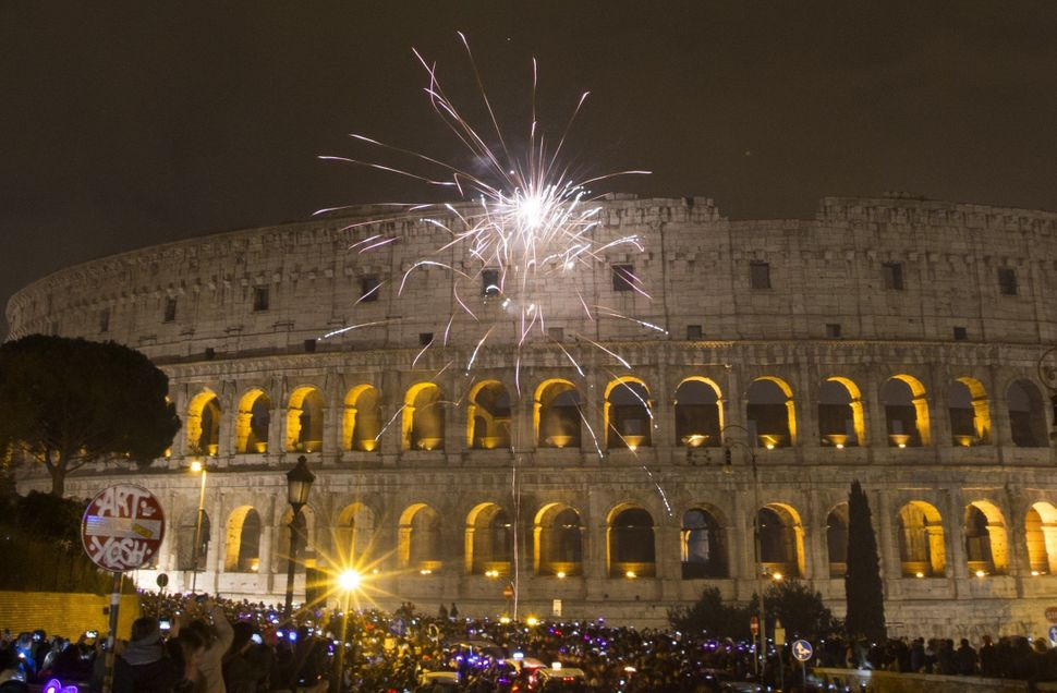ROME, ITALY - JANUARY 1: Revelers celebrate the new year near the Colosseum after the clock strikes midnight in Rome, Italy o
