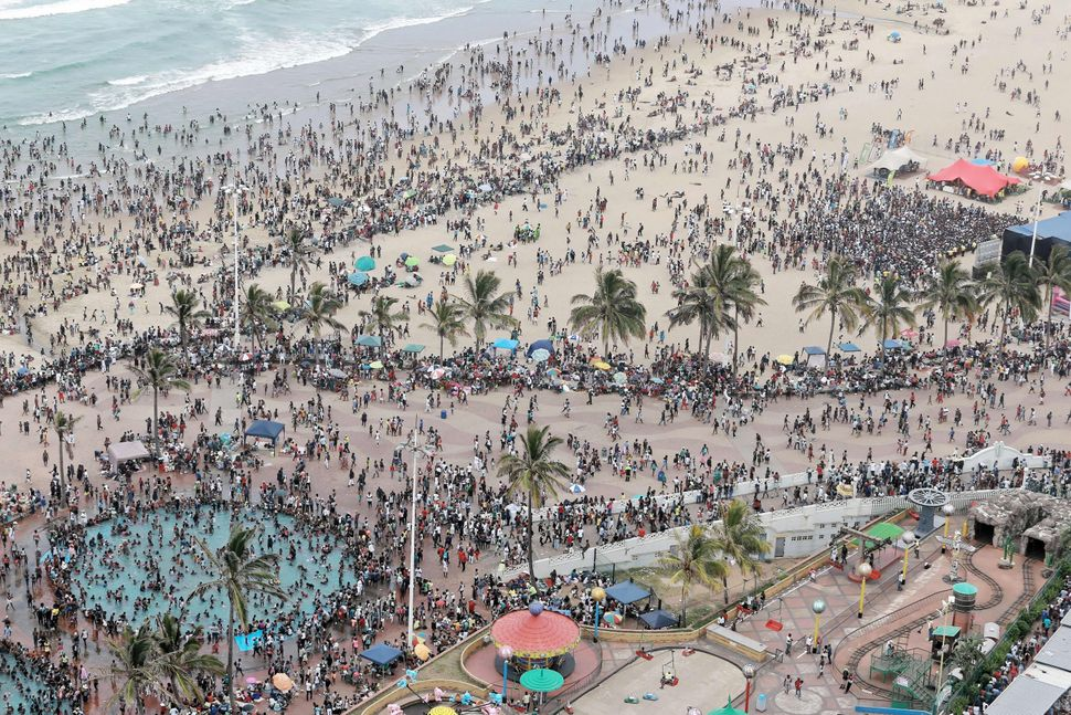 A general view shows New Year party revellers and holidaymakers gathering on the North Pier Beach and the swimming pool durin