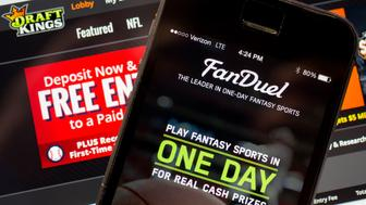 The FanDuel Inc. app and DraftKings Inc. website are arranged for a photograph in Washington, D.C., U.S., on Monday, Oct. 5, 2015. Fantasy sports companies DraftKings Inc. and FanDuel Inc. raised a total of $575 million in July from investors including KKR & Co., 21st Century Fox Inc. and Major League Baseball to attract players to games that pay out millions of dollars in cash prizes in daily contests. Photographer: Andrew Harrer/Bloomberg via Getty Images