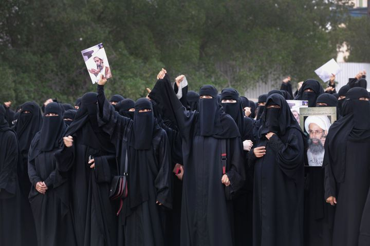 Saudi Shiite women hold placards bearing a portrait of prominent Shiite Muslim cleric Nimr al-Nimr during a protest in the ea