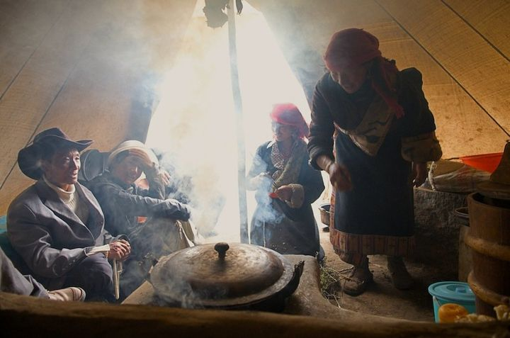 Nomads cook over a yak-dung fire in Qinghai, China.