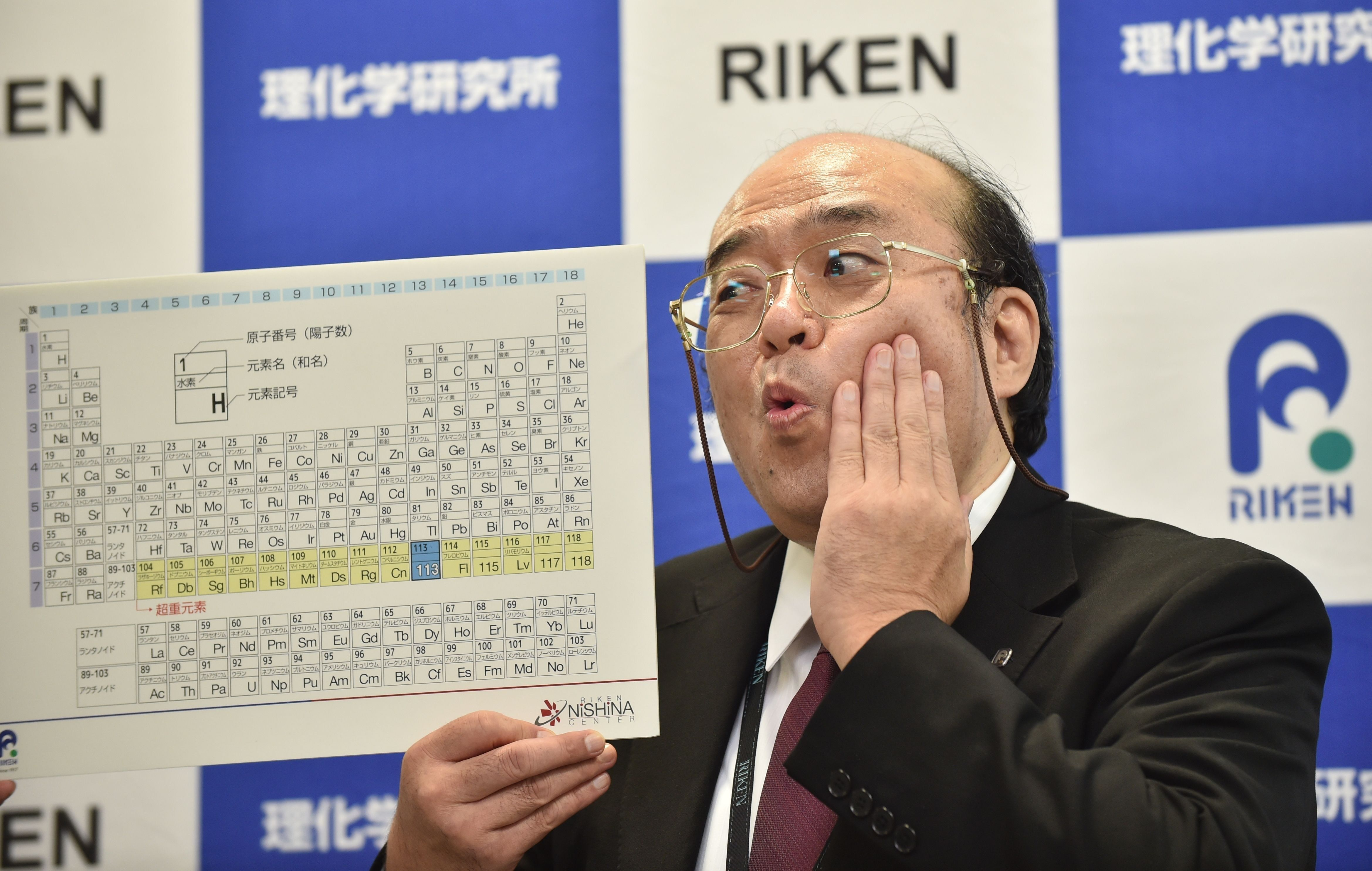 Kosuke Morita, the leader of the Riken team, poses with a board displaying the new atomic element 113 during a press conference in Wako, Saitama prefecture on December 31, 2015. A Japanese research team has received naming rights for new atomic element 113, the first on the periodic chart to be named by Asian scientists, the team's institute said December 31. Japan's Riken Institute said a team led by Kosuke Morita was awarded the rights from global scientific bodies -- the International Union of Pure and Applied Chemistry (IUPAC) and the International Union of Pure and Applied Physics (IUPAP) -- after successfully creating the new synthetic element three times from 2004 to 2012. AFP PHOTO / KAZUHIRO NOGI / AFP / KAZUHIRO NOGI        (Photo credit should read KAZUHIRO NOGI/AFP/Getty Images)