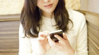 Young woman using smartphone in cafe,mid section