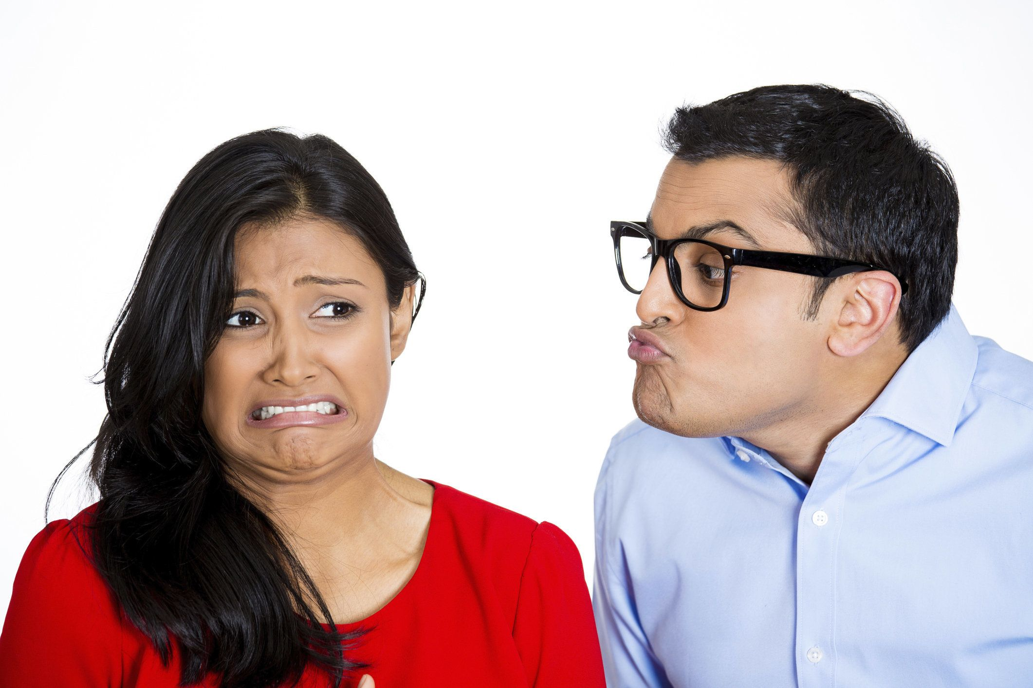 Closeup portrait of nerdy young man with big black glasses trying to kiss snobby woman who is grossed out, disgusted funny smirk on face, isolated white background. Negative emotion facial expression