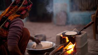 An Indian woman cooks over a traditional stove using wood and cow dung as its fuel.