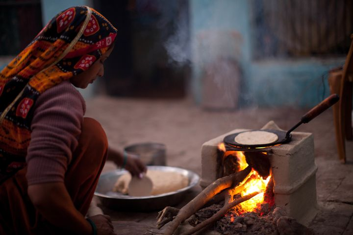 An Indian woman cooks over a traditional stove using wood and cow dung as fuel.