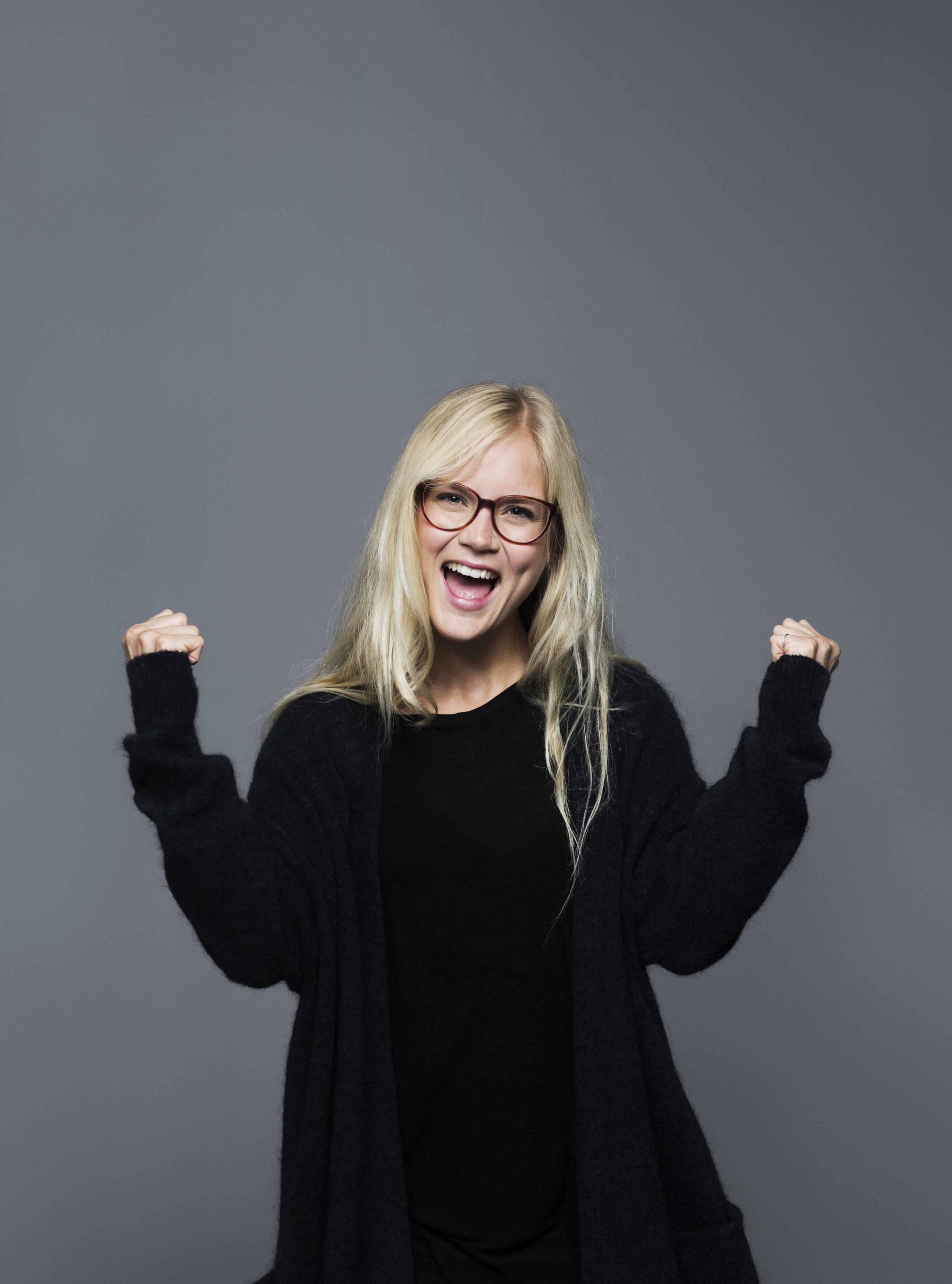 Portrait of young woman dancing, studio background