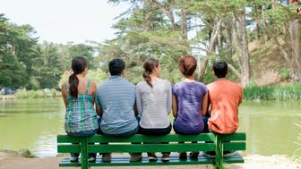 Friends sitting on bench by pond, Golden Gate Park, San Francisco, California