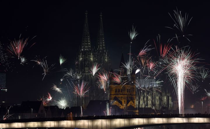 Fireworks explode over the river Rhine in front of the Great Saint Martin Church and the Cologne Cathedral during New Year's