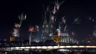 TOPSHOT - Fireworks explode over the river Rhine in front of the Great Saint Martin Church and the Cologne Cathedral during New Year's celebrations in Cologne on January 1, 2016. AFP PHOTO / PATRIK STOLLARZ / AFP / PATRIK STOLLARZ        (Photo credit should read PATRIK STOLLARZ/AFP/Getty Images)