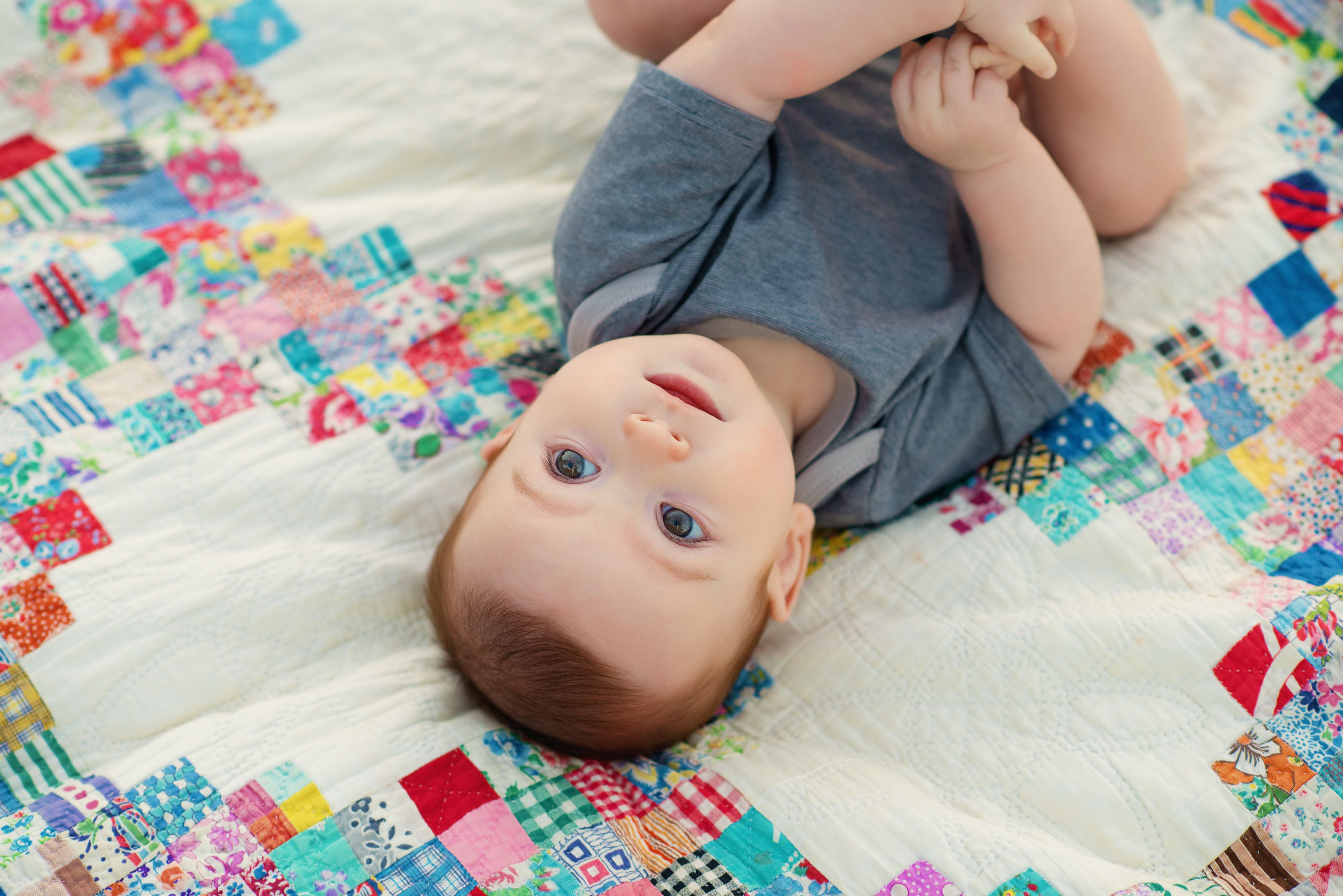 A beautiful baby boy six months old outdoors laying on an antique, hand made quilt.