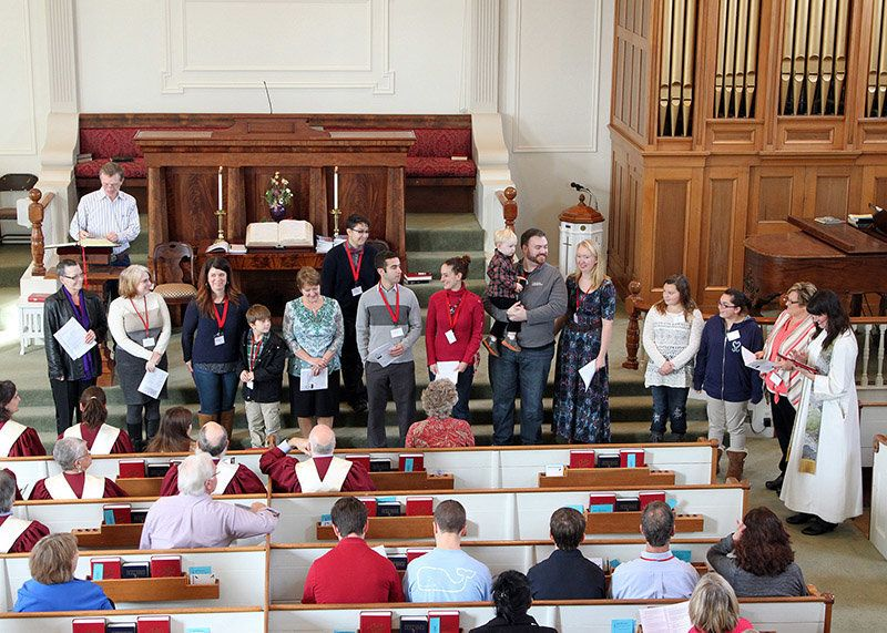 Pastor Robin Bartlett, far right, conducts a new-member ceremony at First Church in Sterling, Mass.