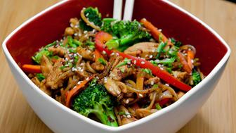 Stir-fired chicken in wok with bell pepper, broccoli, carrot, onion, ginger, chili and garlic served with chow mein noodles drizzled with sesame oil.