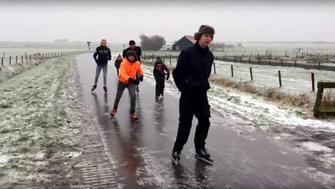 Several people are seen ice skating in the streets of the Netherlands.