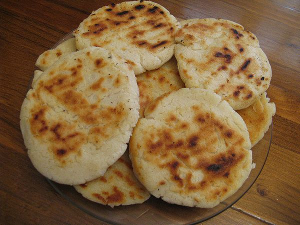 "Arepas, or ""corn cakes,"" are not the sweet baked goods their English translation may indicate. They are to Colombians what to"