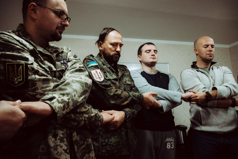 Participants hold hands at a training seminar with Wounded Warrior Ukraine.